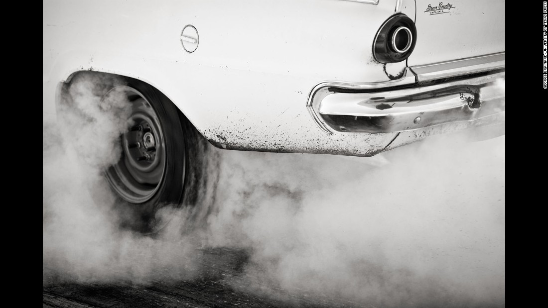 Smoke rises from around the tires of a vintage car at the show.