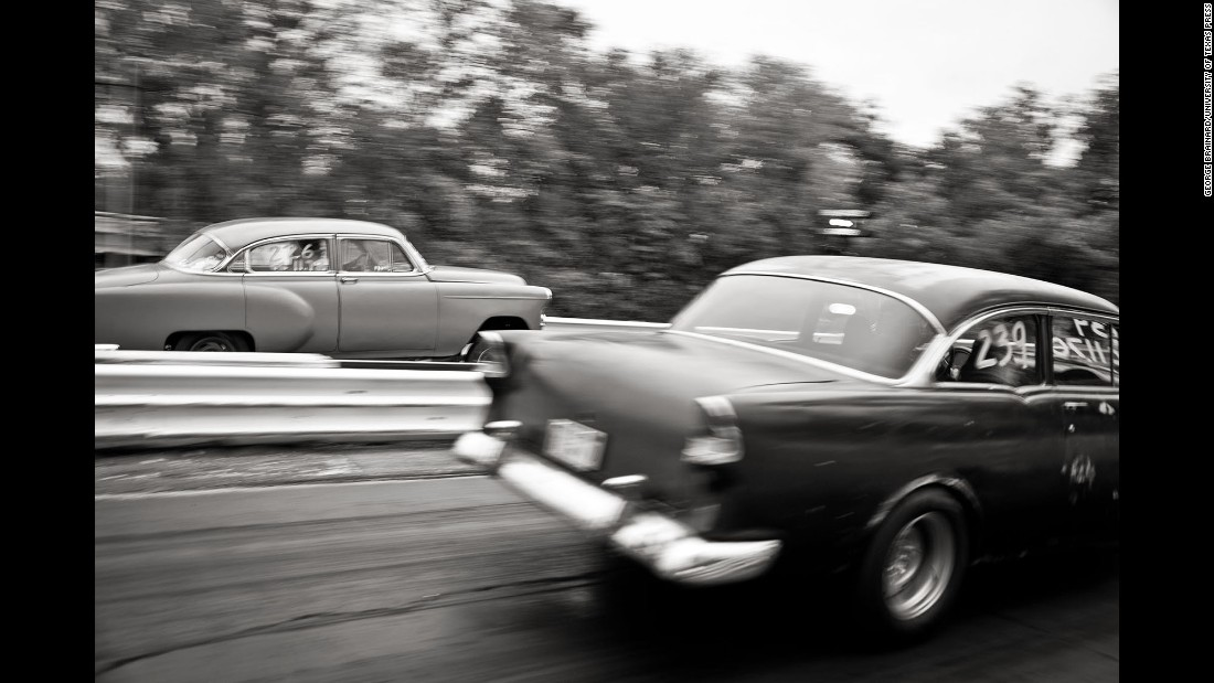 Classic cars race down a stretch of track.