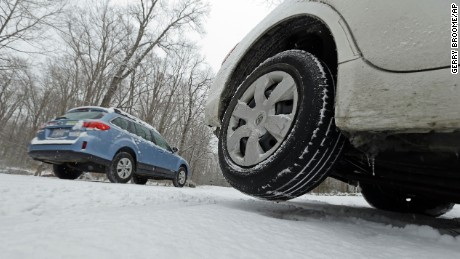 A driver moves slowly past a stranded vehicle at right that slid off of the road in Chapel Hill, N.C., Tuesday, Feb. 24, 2015, after winter weather moved through the area causing numerous accidents and slippery driving conditions. (AP Photo/Gerry Broome)
