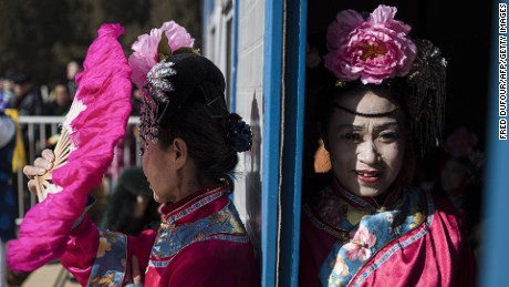 Women wearing traditional costumes wait prior to a show at Ditan Temple Fair during the Chinese Lunar New Year in Beijing on February 25, 2015. Millions of Chinese are celebrating the Spring Festival, the most important holiday on the Chinese calendar, which this year marks the beginning of the Year of the Sheep.