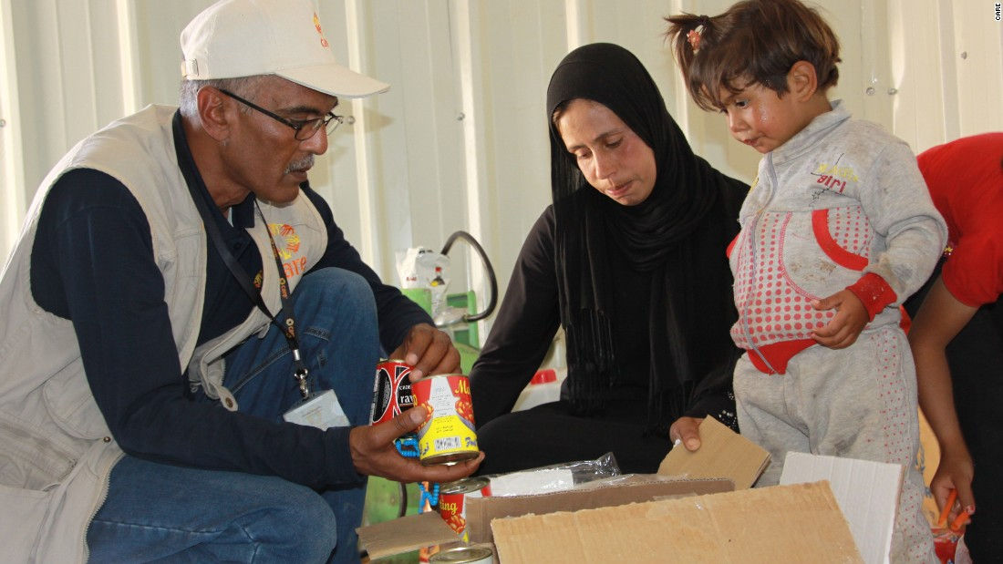 A CARE aid worker distributes food to a Syrian refugee family.  CARE has 230 staff in the Syrian region and has been working on the humanitarian crisis since the beginning.