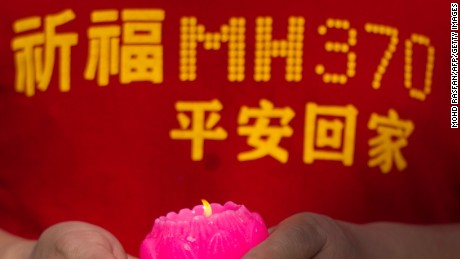 A relative of one of the Chinese passengers from the missing Malaysia Airlines flight MH370 holds a candle before offering prayers at Thean Hou Temple in Kuala Lumpur on March 1, 2015. The visit to the temple comes nearly a year after Malaysian Airlines MH370 went missing en route from Kuala Lumpur to Beijing with 239 people on board in March 2014. AFP PHOTO / MOHD RASFAN (Photo credit should read MOHD RASFAN/AFP/Getty Images)