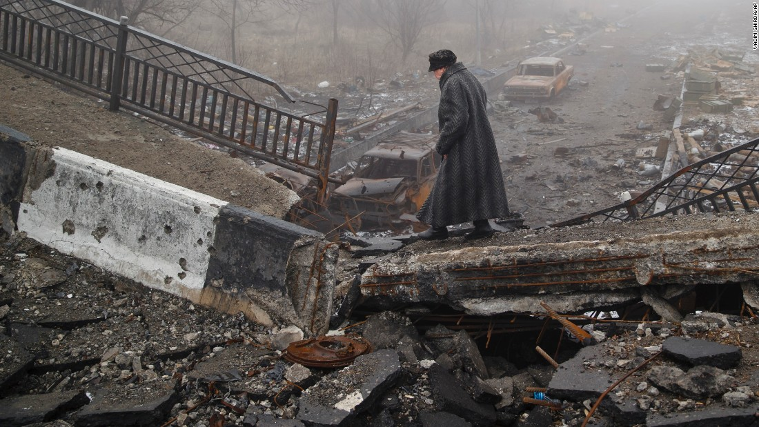 A woman makes her way across a  bridge destroyed in heavy fighting in Donetsk, Ukraine, on March 1.
