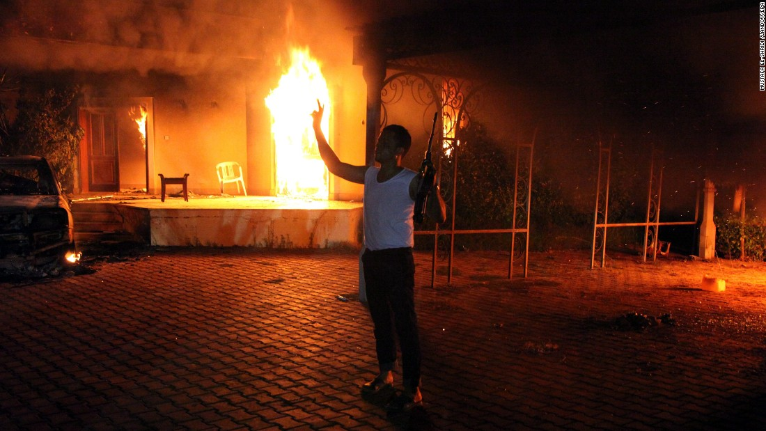 An armed man stands next to buildings set on fire at the U.S. consulate in Benghazi, Libya, on September 11, 2012. U.S. Ambassador J. Christopher Stevens and three other U.S. nationals were killed in the attack.