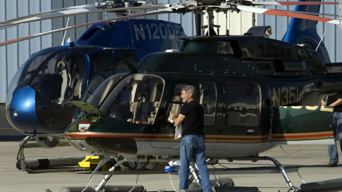 Ford checks and cleans the windows of his helicopter before flying on January 29, 2011.