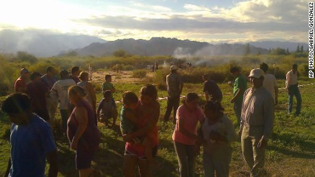 People gather close to the smoking wreckage near Villa Castelli, Argentina.