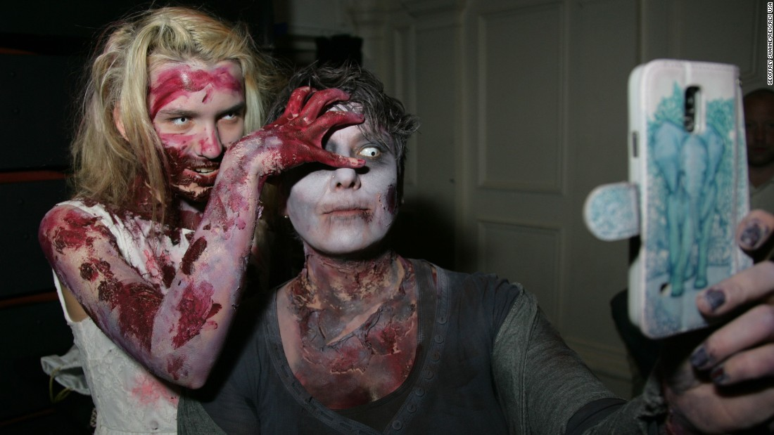 People dressed as zombies take a selfie Saturday, March 7, at the Windsor Zombie Walk in Windsor, England.