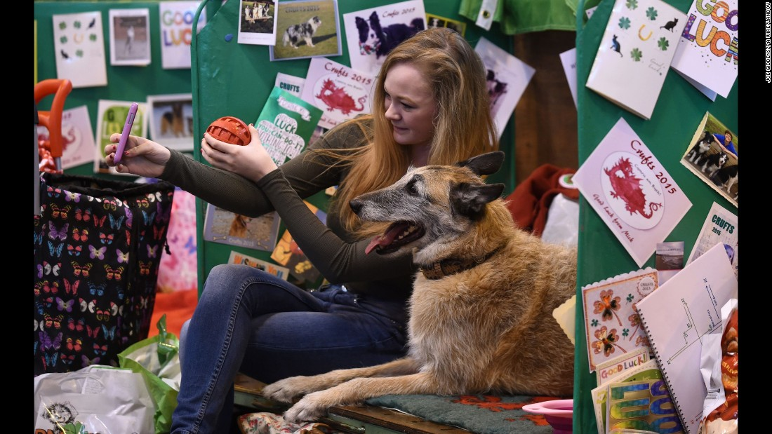Emily George takes a photo with her Belgian shepherd, Byre, during the Crufts dog show in Birmingham, England, on Thursday, March 5.