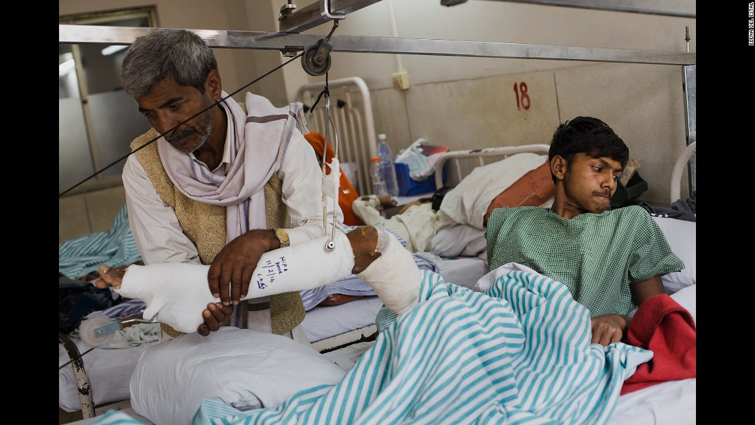 Dharmender's father, Mahaveer, helps him to move on the bed a few days after his operation.