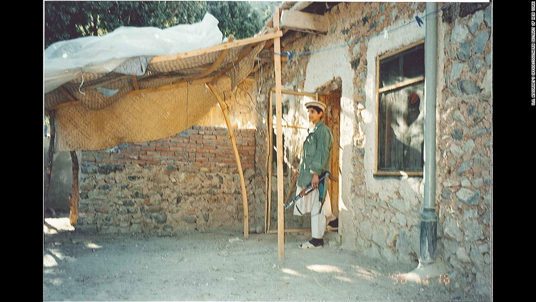 A young man stands outside the house.