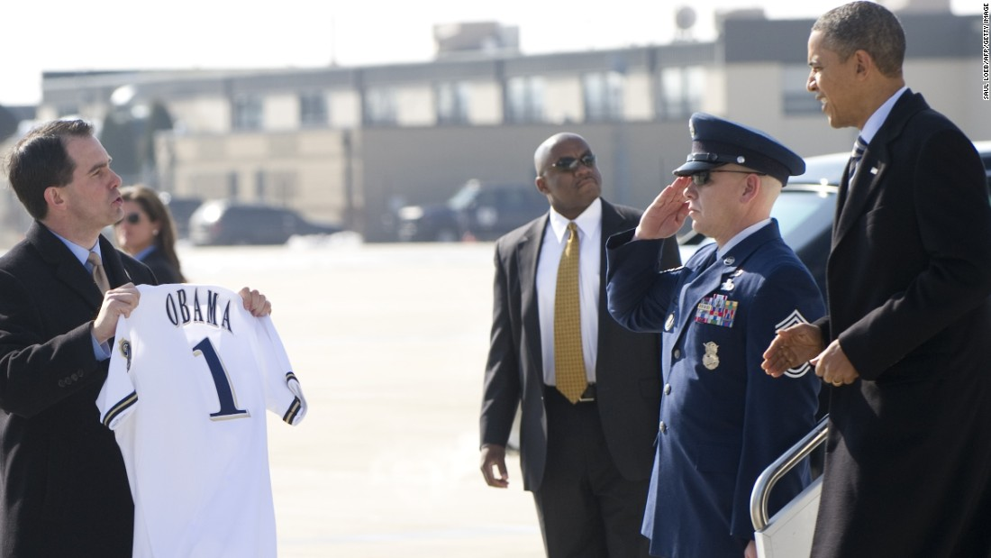 President Barack Obama receives a Milwaukee Brewers baseball jersey from Walker (left) as he disembarks from Air Force One upon arrival at General Mitchell International Airport in Milwaukee, Wisconsin, February 15, 2012.