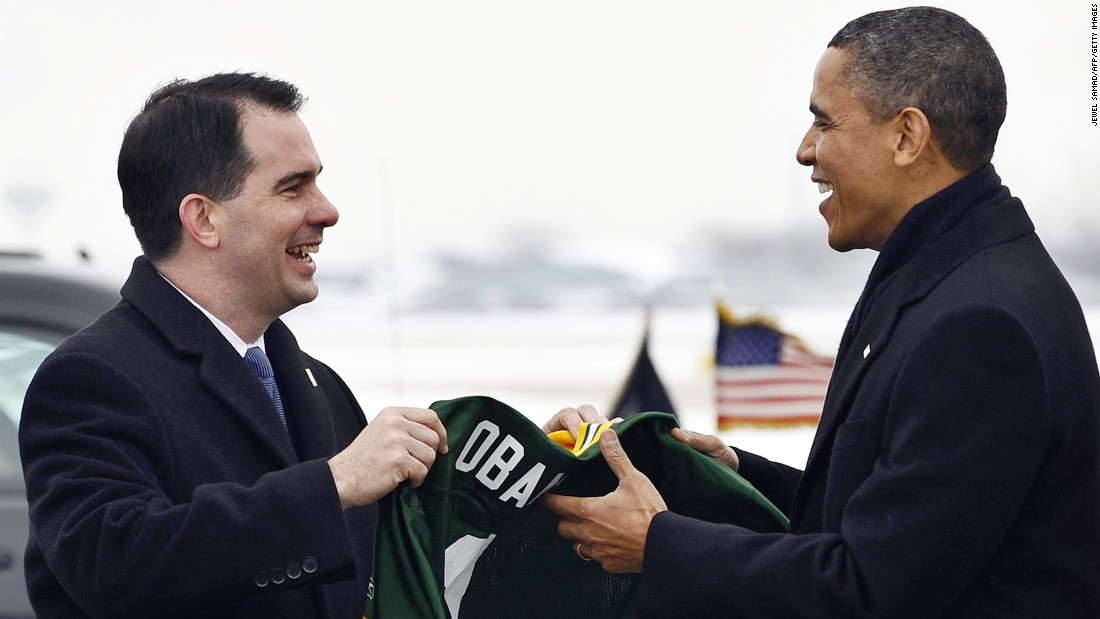 President Obama receives a Green Bay Packers NFL football team jersey with 'Obama #1' written on it from Walker (left) at Austin Straubel International Airport in Green Bay, Wisconsin, on January 26, 2011.