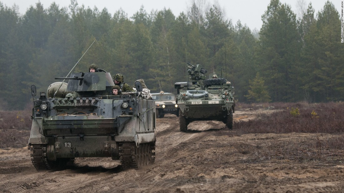 Lithuanian soldiers, left, of 3rd Company, Algirdas Mechanized Infantry Battalion, advance in a M113 armored personnel carrier with U.S. Troopers from 3rd Platoon, Lightning Troop, 3rd Squadron, 2nd Cavalry Regiment, following close behind at Pabrade Training Area, Lithuania, March 2, 2015.