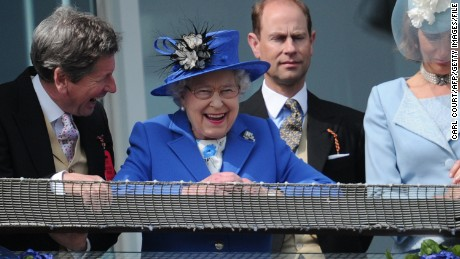 Britain's Queen Elizabeth II (C) standing next to Prince Edward, Earl of Wessex (2R) smiles from the royal balcony as she looks down on the winning horse in the Derby race on Derby Day, the second day of the Epsom Derby horse racing festival, at Epsom in Surrey, southern England, on June 2, 2012 the first official day of Britain's Queen Elizabeth II's Diamond Jubilee celebrations. AFP PHOTO / CARL COURT (Photo credit should read CARL COURT/AFP/GettyImages)