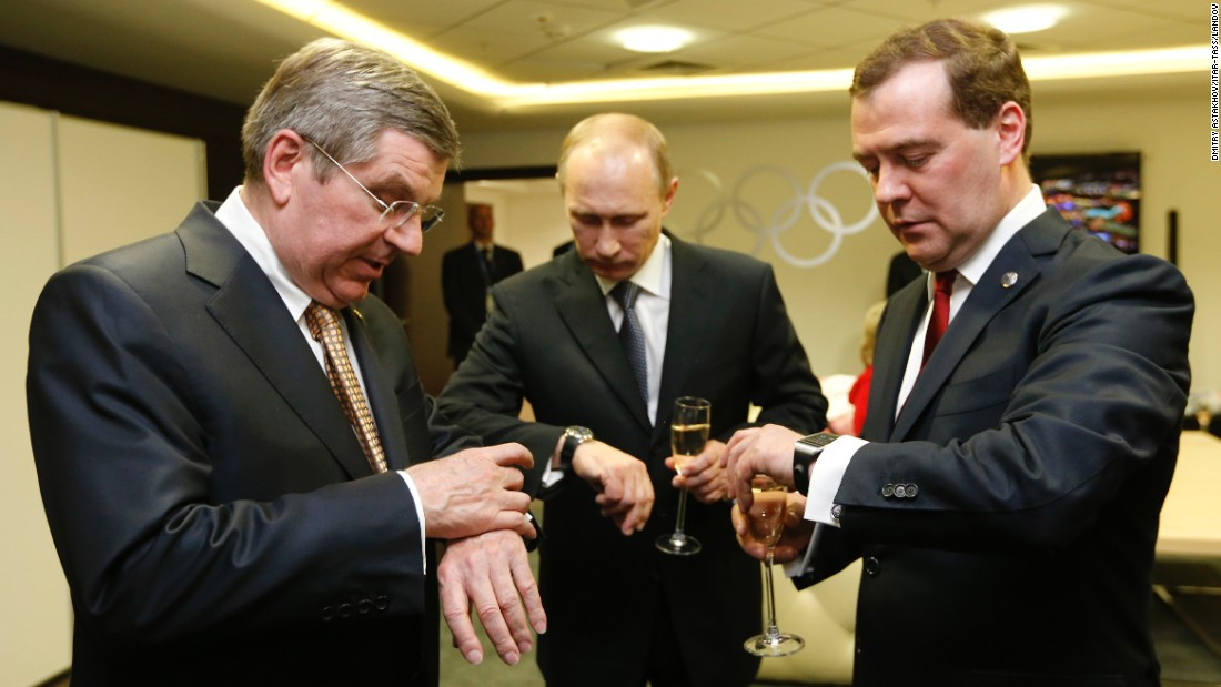 From left, International Olympic Committee President Thomas Bach, Putin and Medvedev look at their watches before the closing ceremony of the Winter Olympics in February 2014.