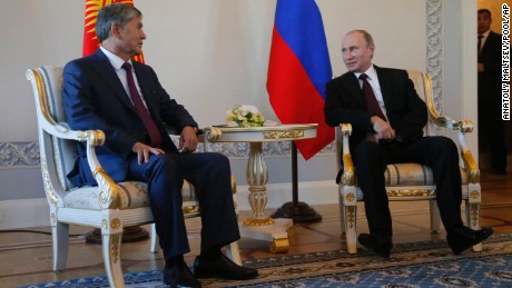 Russian President Vladimir Putin, right, and Kyrgyz President Almazbek Atambayev speak during their meeting in the Konstantin Palace outside St. Petersburg, Russia, Monday, March 16, 2015. Putin resurfaced Monday after a 10-day absence from public view, looking healthy. (AP Photo/Anatoly Maltsev, Pool)