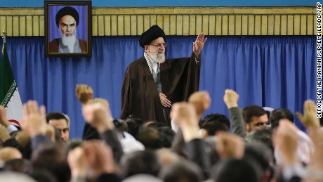 In this picture released by an official website of the office of the Iranian supreme leader, Supreme Leader Ayatollah Ali Khamenei waves while attending a meeting with a group of environmental officials and activists at his residence in Tehran, Iran, Sunday, March 8, 2015. A portrait of the late revolutionary founder Ayatollah Khomeini hangs in background. (AP Photo/Office of the Iranian Supreme Leader)