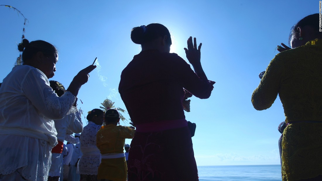 MARCH 17 - BALI, INDONESIA: Women offer prayers during a religious ceremony called Melasti. The ritual, in which the faithful carry a holy Hindu symbol to the sea to be purified, is performed ahead of the Hindu Day of Silence.