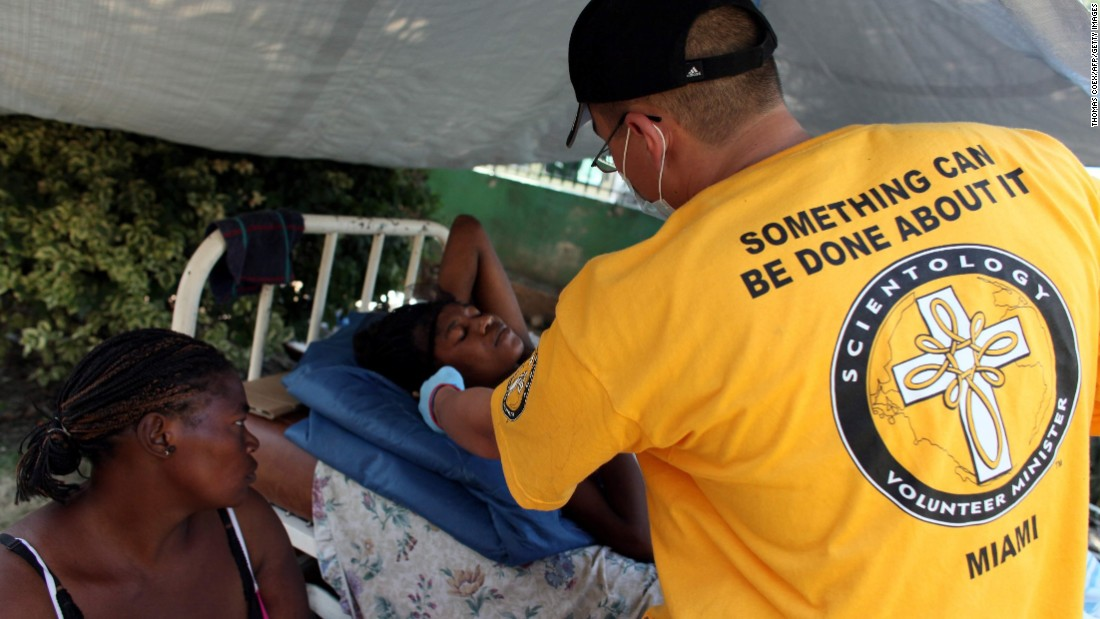 A volunteer from the Church of Scientology touches an injured woman in Port-au-Prince, Haiti, after the devastating earthquake there in January 2010.