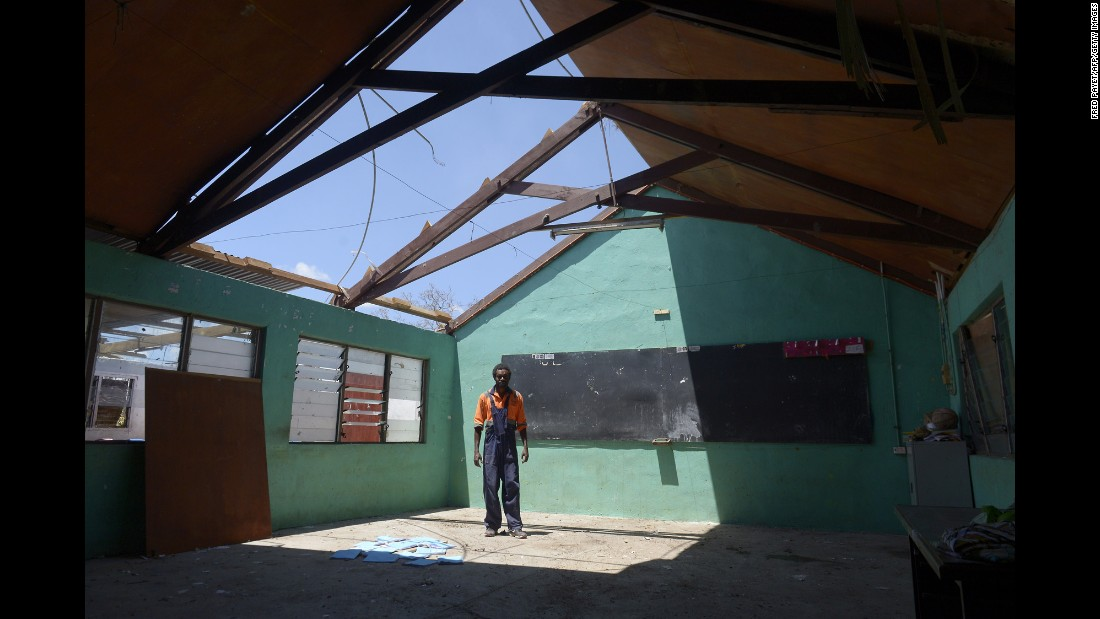 A man stands under the damaged rooftop of a school in Vanuatu's capital, Port Vila, on March 18.