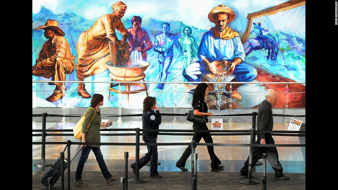 Travelers walk through security past a mural at Denver International Airport. Despite the criticisms, SPOT remains in place and has cost taxpayers well over $1 billion since its inception in 2007. The SPOT program should be terminated, Handeyside says.