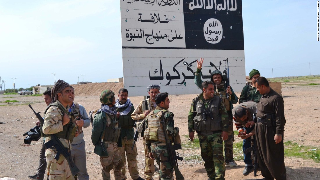 Peshmerga fighters stand next to an ISIS sign at the entrance to the northern Iraqi town of Hawija, south of Kirkuk in March 2015 after they reportedly re-took the area from ISIS jihadists.