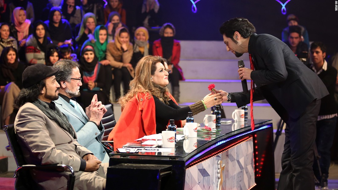 Singer Arash Barez gives a flower to a judge on International Women's Day.
