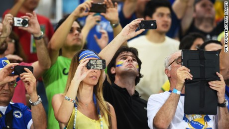 CUIABA, BRAZIL - JUNE 21:  Fans look on with electronic devices during the 2014 FIFA World Cup Group F match between Nigeria and Bosnia-Herzegovina at Arena Pantanal on June 21, 2014 in Cuiaba, Brazil.  (Photo by Stu Forster/Getty Images)