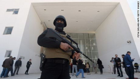 A member of the Tunisian security forces stands guard as journalists gather at the visitors entrance of the National Bardo Museum in Tunis on March 19, 2015, in the aftermath of an attack on foreign tourists.