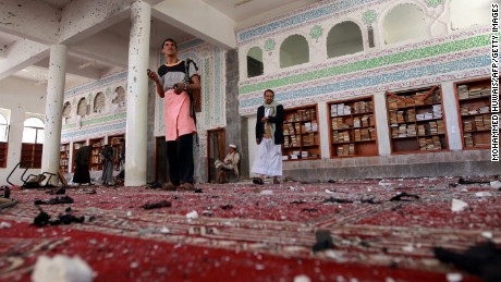 Armed men inspecting the damage following a bombing at the Badr mosque in Sanaa on March 20, 2015.