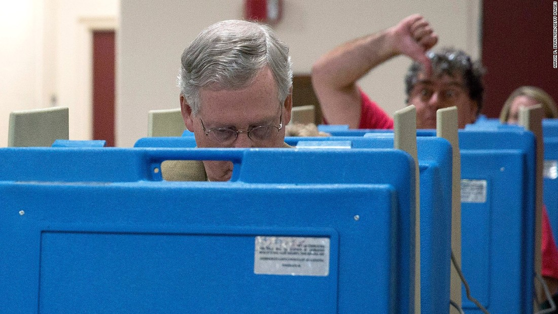 A voter gives a thumbs-down as McConnell votes in the midterm elections in November 2014 in Louisville, Kentucky.