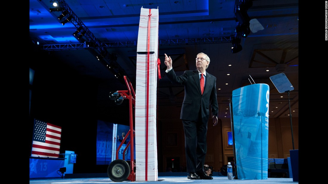 McConnell points to a stack of papers representing what he says are the regulations associated with the Affordable Care Act as he speaks at the 2013 CPAC in National Harbor, Maryland.