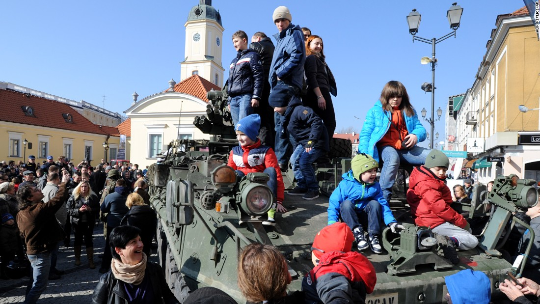 People surround a group of U.S. Army armored vehicles from the 3rd Squadron, 2nd Cavalry Regiment, on March 24 in Bialystok. The convoy started in Estonia and passed through Latvia and Lithuania before entering Poland on its way to a base in Germany.