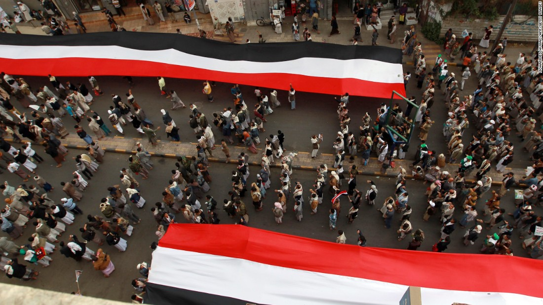 "Houthi supporters in Sanaa deploy giant national flags Wednesday, March 18, during a demonstration to mark the fourth anniversary of the ""Friday of Dignity"" attack. In 2011, forces loyal to Saleh <a href=""http://www.cnn.com/2011/10/15/world/meast/yemen-unrest/"" target=""_blank"">opened fire on protesters</a> who had gathered in Sanaa to demand the ouster of Saleh and his regime."