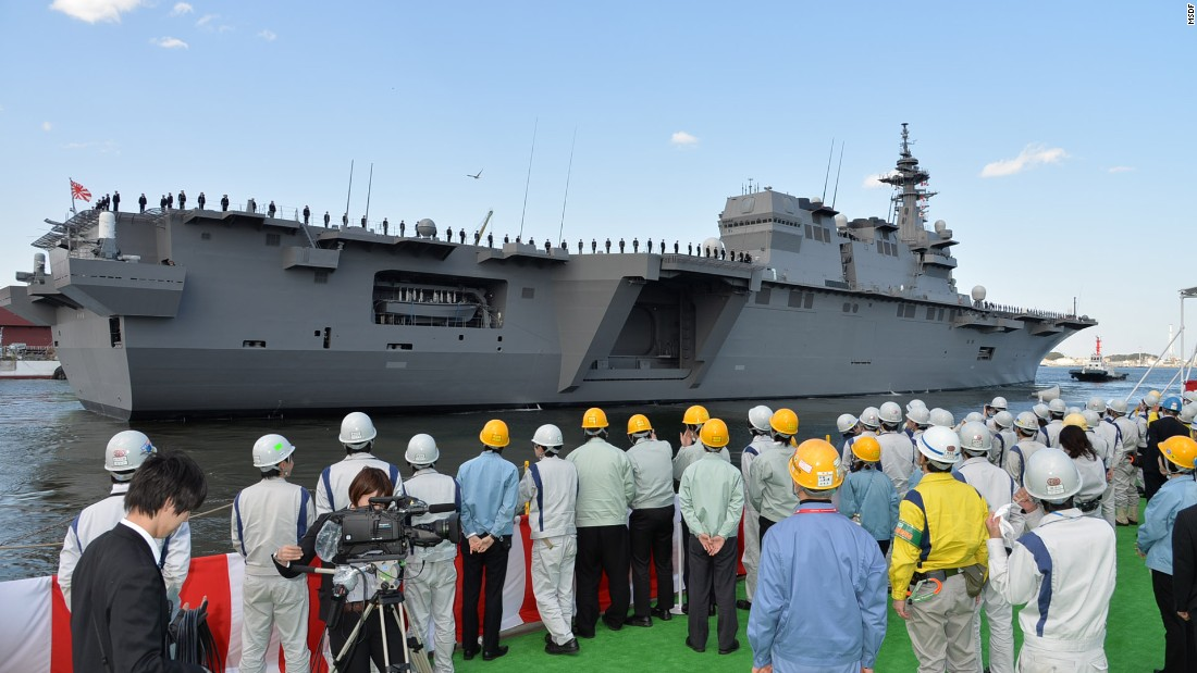 Workers look on at Japan's newest -- and biggest -- warship, the Izumo, moored in Yokosuka, Kanagawa prefecture. It's the largest Japanese military vessel since World War II.