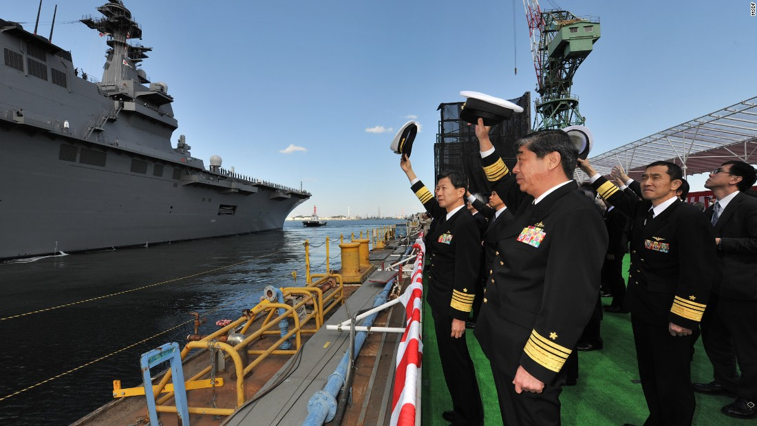 MSDF officials take part in a ceremony marking the commissioning of Japan's new Izumo helicopter carrier.