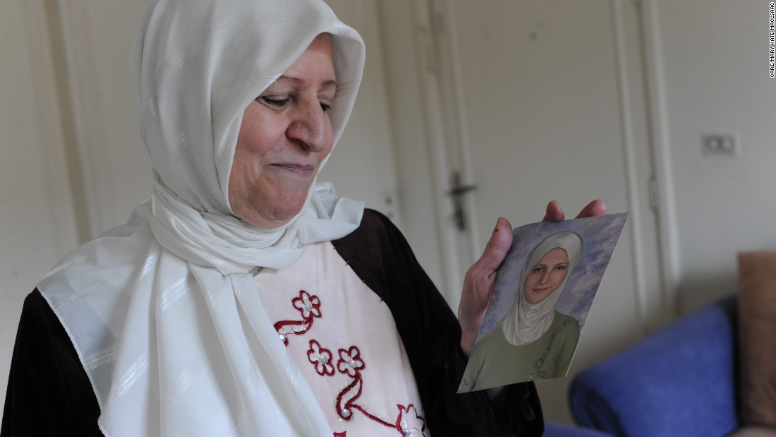 Hiba's mother, Hanan, looks at a photograph of her daughter the year she graduated from high school.  Hiba was just a couple of classes away from graduating from university when the family was forced to leave their home.