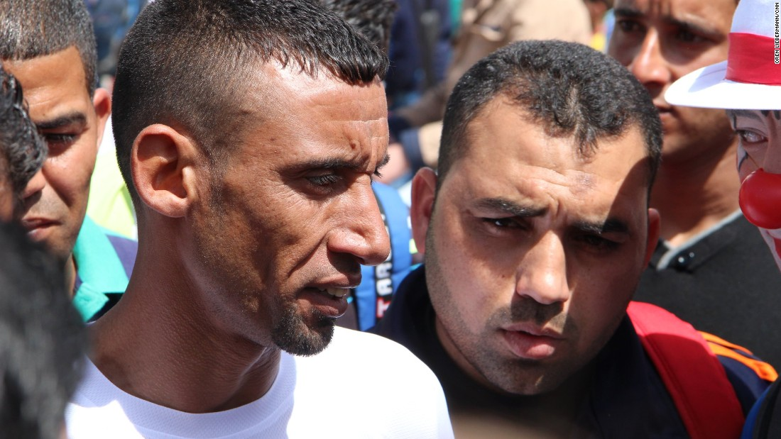 Men's marathon winner Nader al-Masri, left, is surrounded by a crowd at the finish.
