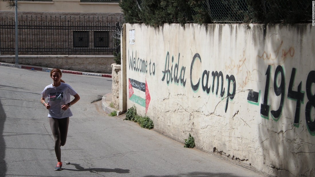 A runner passes by the entrance to the Aida refugee camp in Bethlehem.