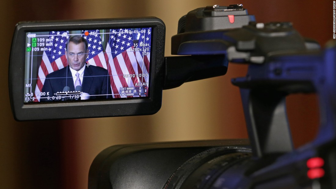 The image of the Speaker of the House John Boehner (R-OH) is displayed in a monitor of a camera as he talks with reporters in his office in the Capitol in November 2014 in Washington.