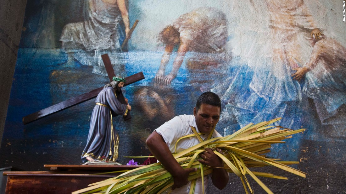 A church volunteer carries an armful of palm fronds to be given to parishioners at the Metropolitan Cathedral in Managua on March 29.