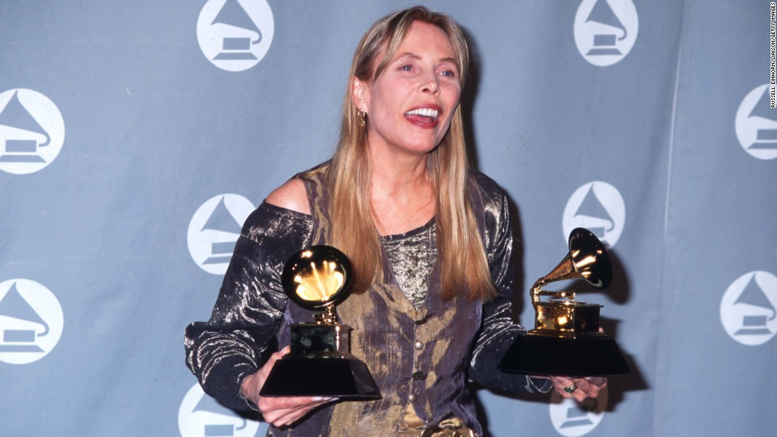 "Mitchell holds her two Grammys after the 1996 award ceremony in Los Angeles. She won the best pop album and best recording package awards for ""Turbulent Indigo."" The singer-songwriter has won eight Grammys in her career."