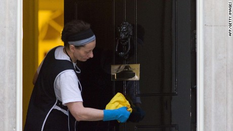 A cleaner polishes the door of number 10 Downing Street in London on March 30, 2015.