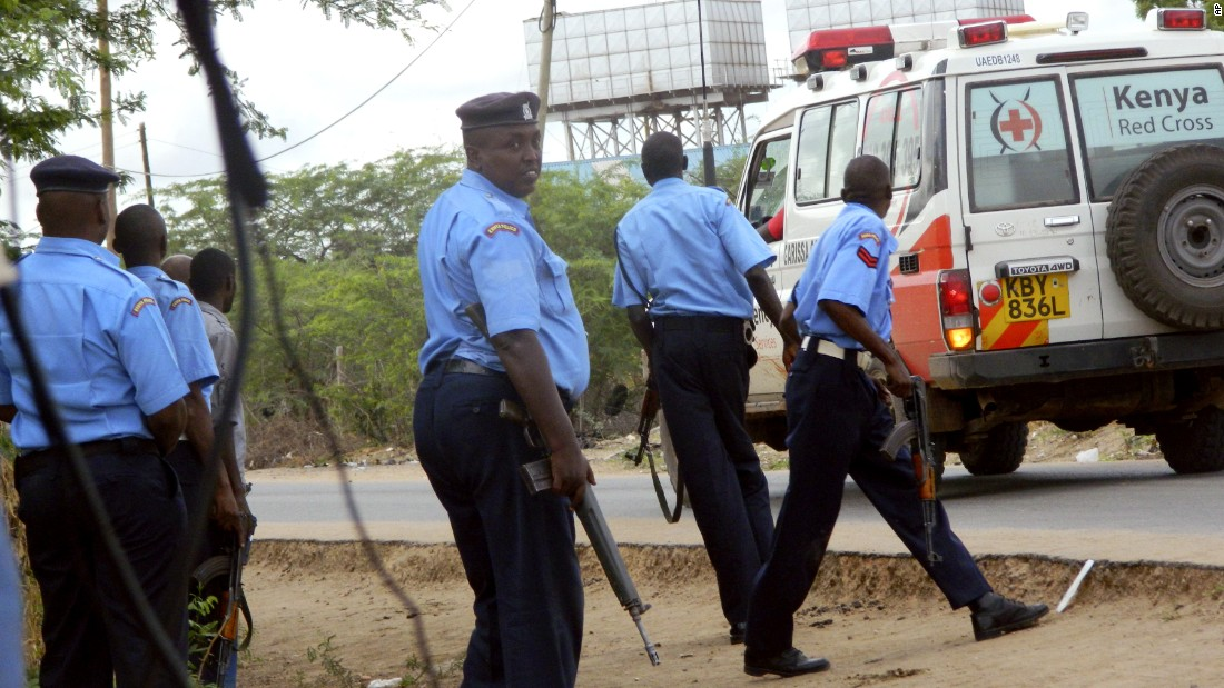 Police officers take positions outside the school as an ambulance carries victims to a hospital in Garissa.