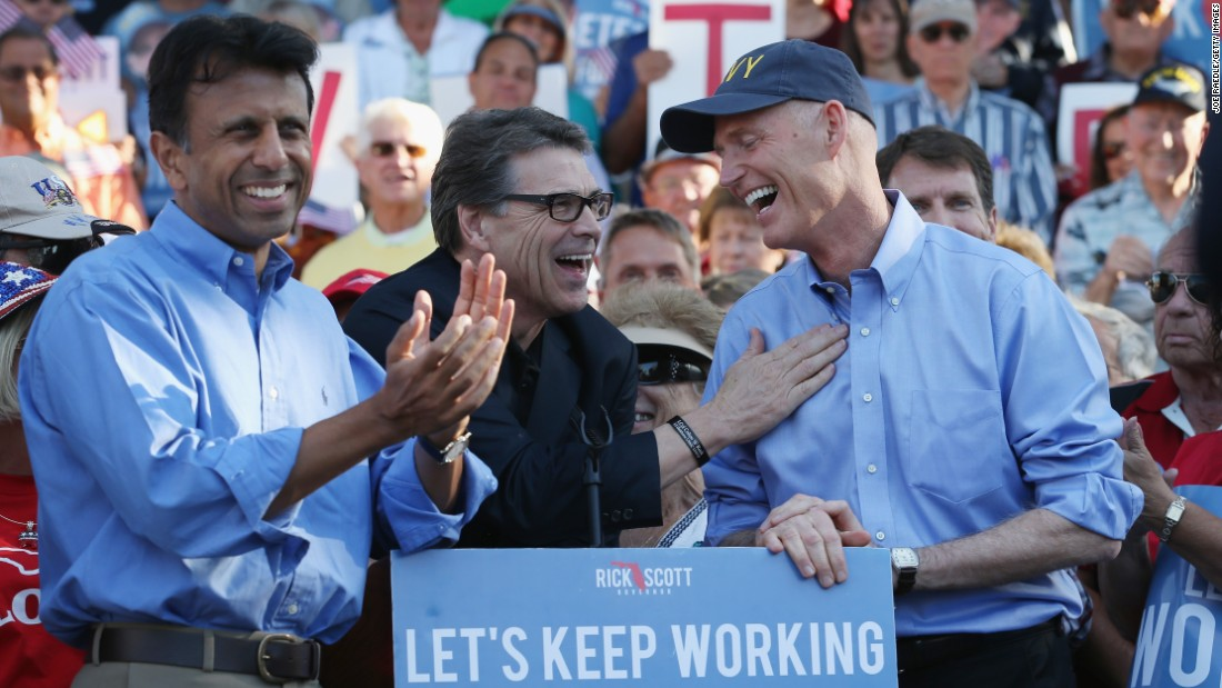 Jindal and Texas Gov. Rick Perry (center) campaign with Florida Gov. Rick Scott on November 3, 2014, in The Villages, Florida.