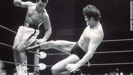 5 Jul 1976: Muhammad Ali fends off a kick from wrestler Antonio Inoki during an exhibition fight in Tokyo, Japan. \ Mandatory Credit: Allsport Hulton/Archive