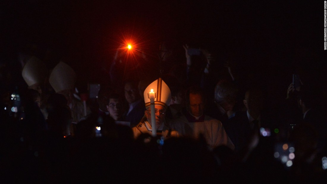 Pope Francis holds a candle during the Easter vigil at St. Peter's Basilica in the Vatican on Saturday, April 4.