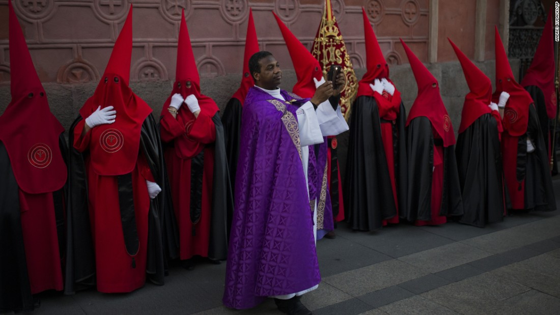 "A priest takes a photo as penitents stand during a procession of  ""La Soledad"" in Madrid, Spain, on April 4. Hundreds of such processions take place throughout Spain."