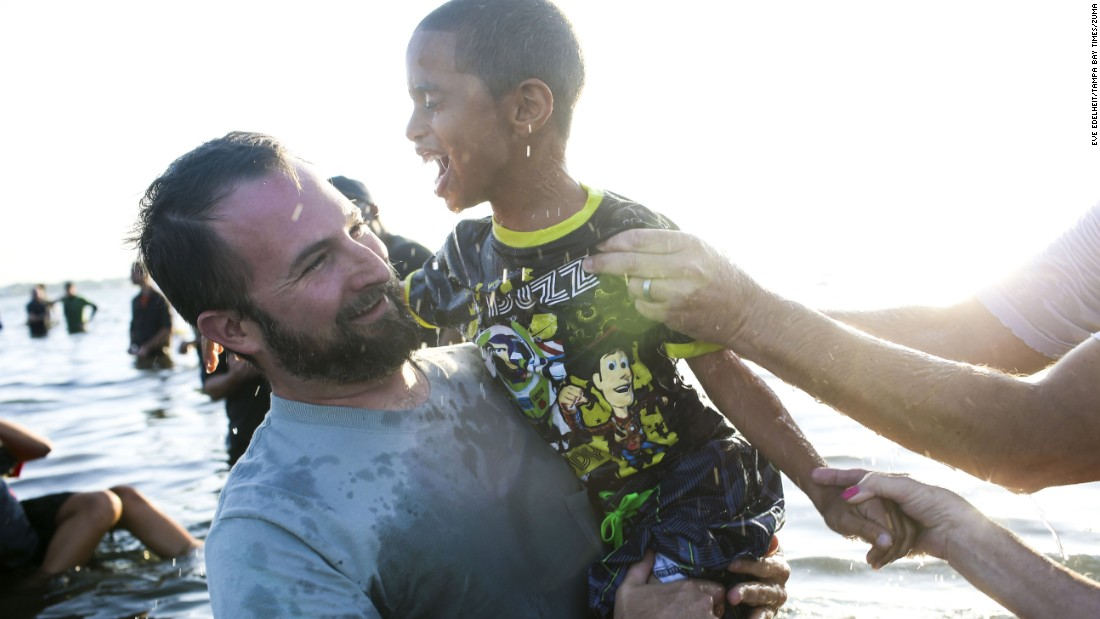 Pastor Ryan Marr holds DaShawn Murzyn, 7, after he was baptized during Calvary Chapel's Sonrise Baptism Service on Easter morning in a park in St. Petersburg, Florida. The church has been doing the baptism service for 30 years and had 150 people signed up to be baptized in the bay this year.