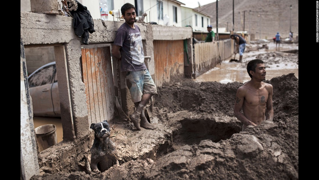 A man digs a gutter to drain water from his house in Copiapo on Monday, March 30.